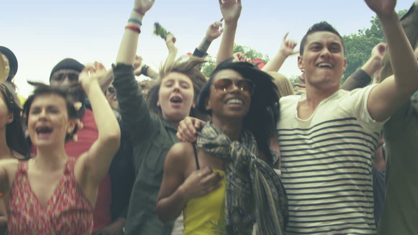 Young crowd of teenagers dancing at a music festival in summer