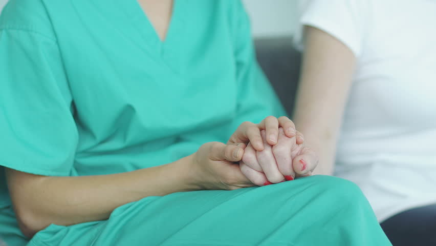 Selective focus as the camera pans from hands to nurse to patient to doctor and back. Couple comforted by caring nurse. A hospital waiting area where patients can by seen by doctors and nursing staff.