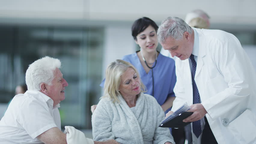 Woman comforted by caring medical staff. Assisting people when life throws unexpected obstacles in your way. A hospital ward or waiting area where patients can by seen by doctors and nursing staff. | Shutterstock HD Video #4503800