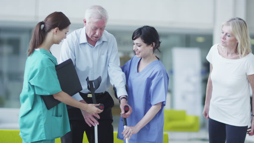 Caring doctors and nurses with patients in a modern hospital