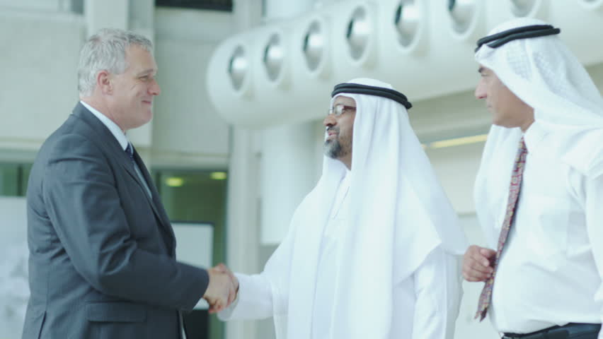Airport security, customs agent or lawyer shaking hands with with two middle eastern businessmen in a waiting area