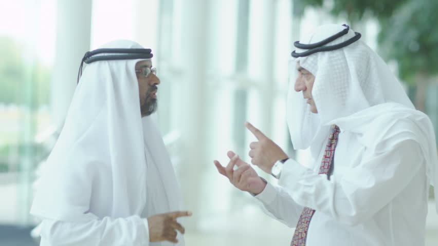 Two middle eastern businessmen shake hands in an airport