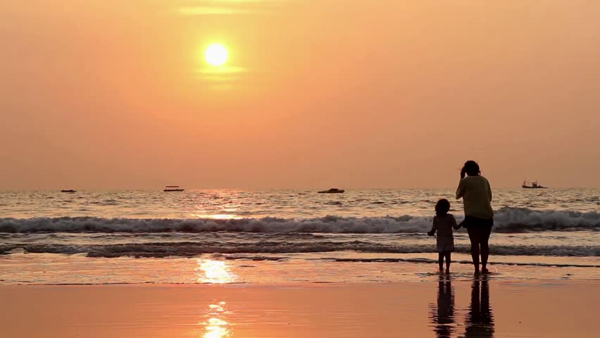 Mom and daughter on the beach, sunset. - HD stock video clip