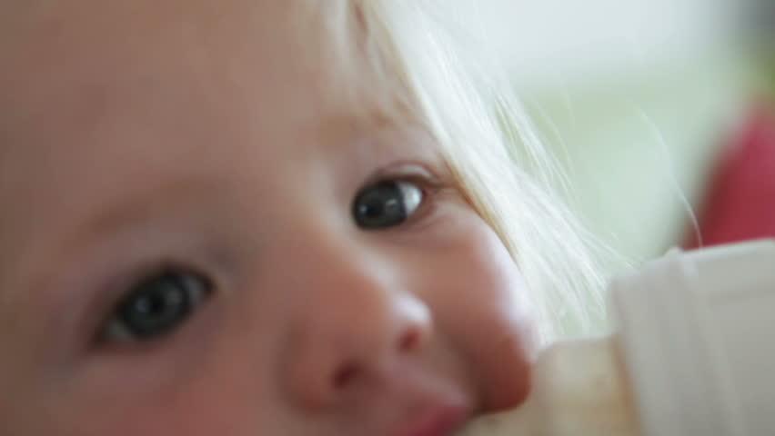 Cute blonde baby girl drinking milk from a bottle.