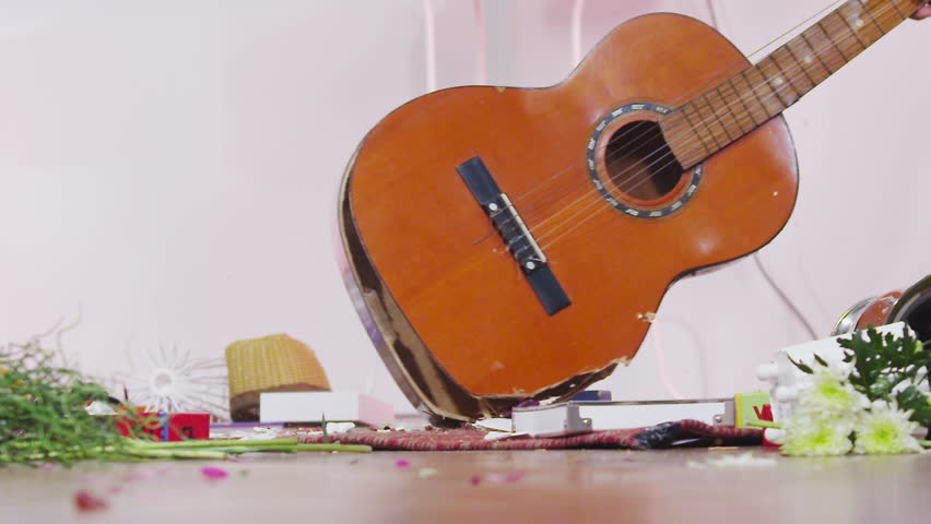 Slow motion shot of acoustic guitar being smashed in rage.