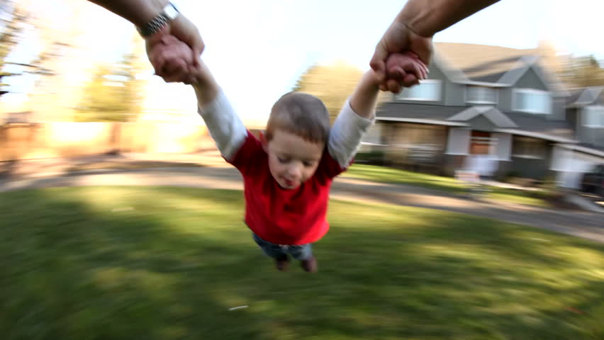 Young boy spinning around in parent's hands