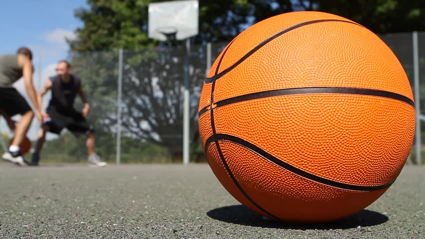 Blurred Basketball One on One Players on a Sunny Day with Basketball in focus in the foreground - HD stock footage clip