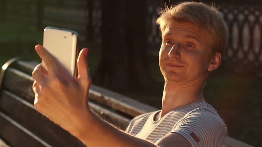 Funny blond man taking photo himself in park for social networks