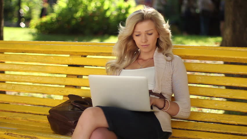 Young business woman with laptop working smiling park bench