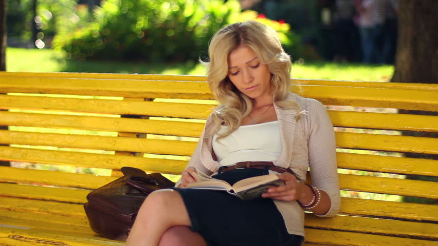 Young adult woman girl reads book in park yellow bench waiting - HD stock video clip