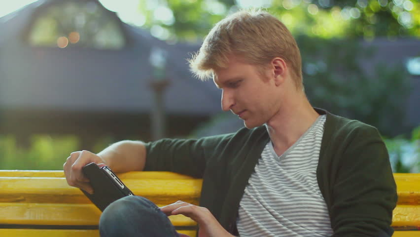 Young blond male reading tablet pc electronic book in park bench