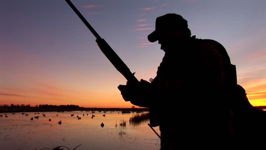 Duck hunter loading gun at sunrise.