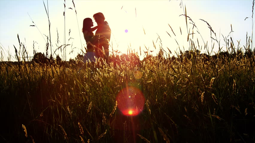 A silhouetted couple hug, kiss and then walk in a wide open golden field at sunset  - HD stock footage clip