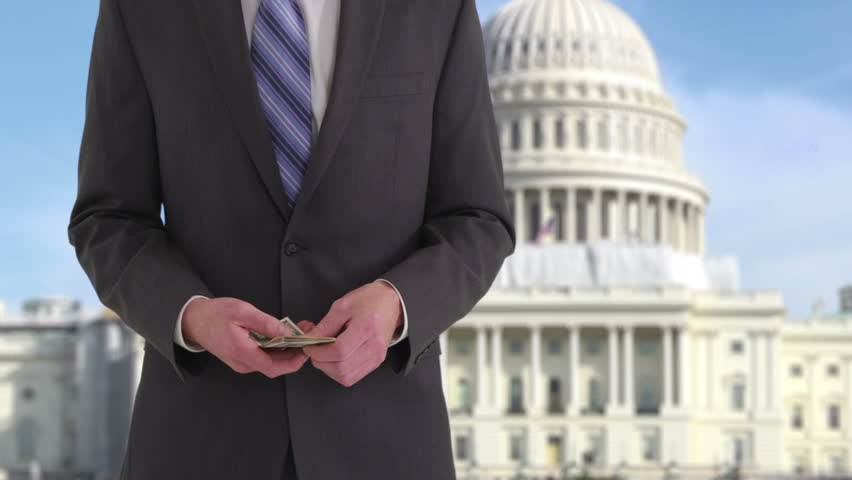 Politician with money in front of US Capitol building