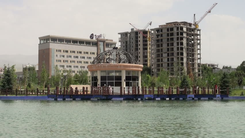 DUSHANBE, TAJIKISTAN - 16 JUNE 2013: People walk past an artificial lake with an office block and a building under construction in the background, in Dushanbe - HD stock footage clip