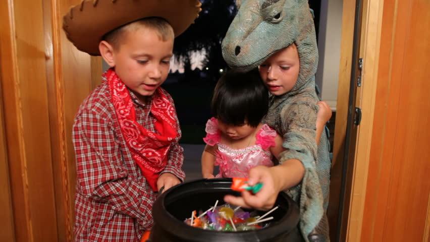 Three children grab Halloween candy
