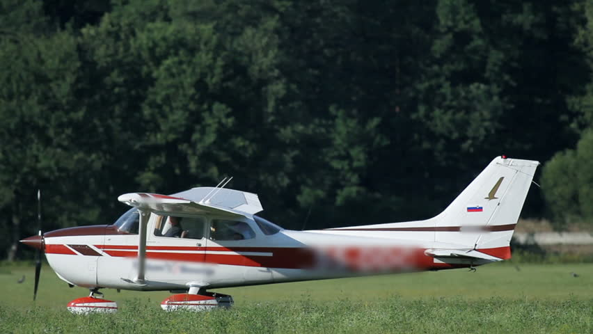 Small airplane with red stripes driving around - HD stock footage clip