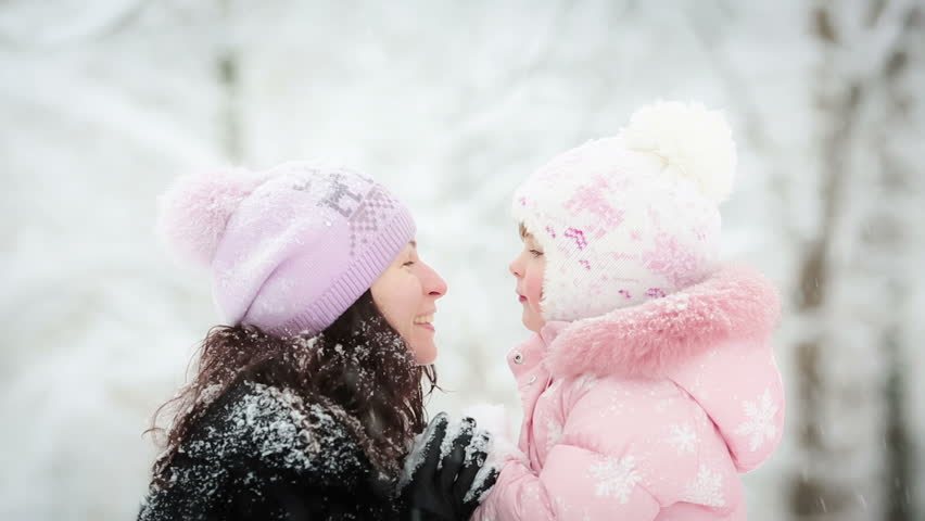 Happy woman and child playing with snow in winter park - HD stock footage clip