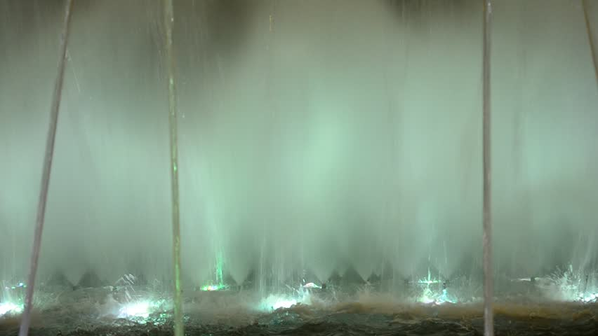 Abstract lit water fountain background of dancing forms.  Night shoot of water spray and jet forming an abstract forms and changing a color - HD stock video clip