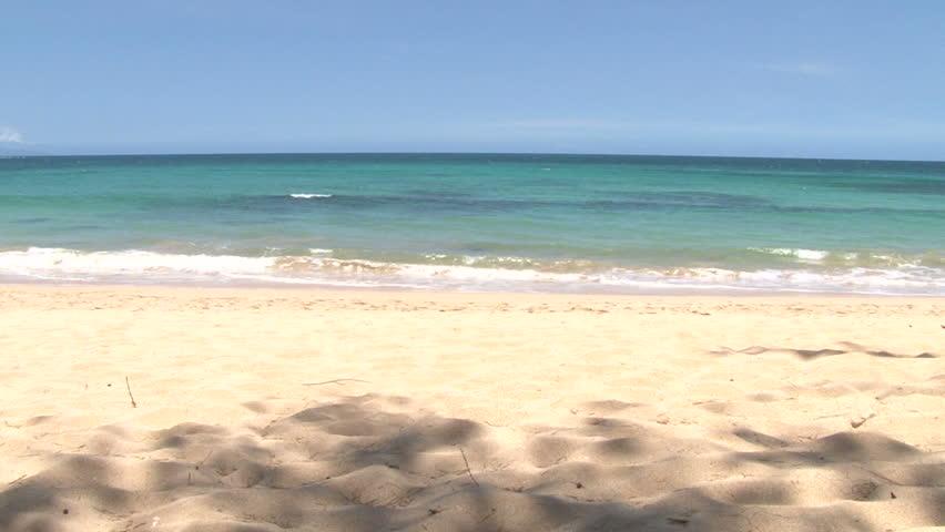 Waves crashing gently on quiet sandy beach in Maui, Hawaii, camera tilt down.