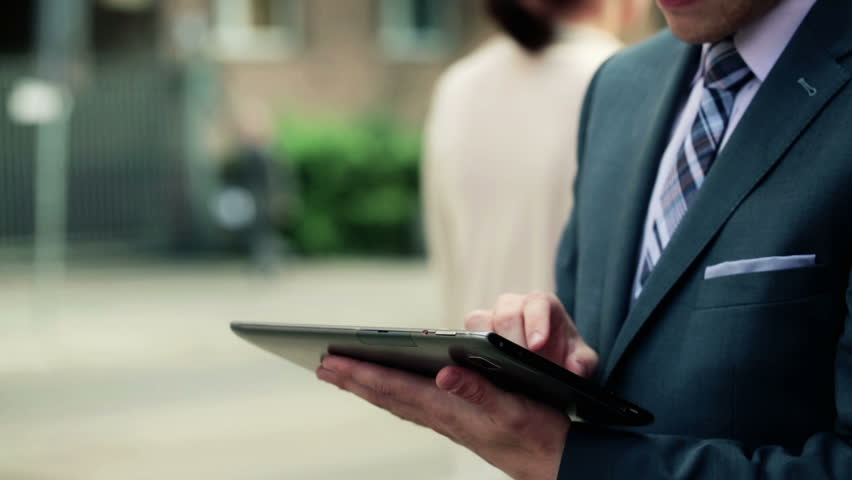 Businessman working on tablet computer by the street