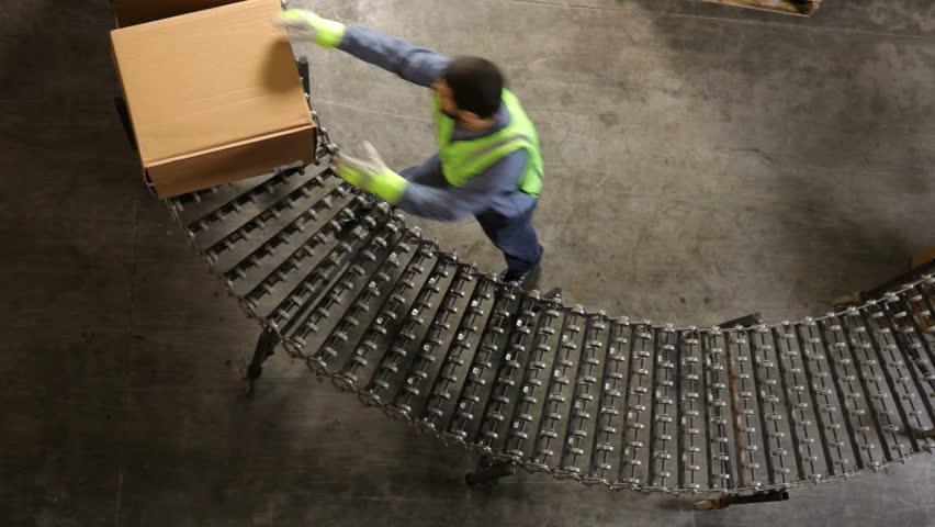 Man in shipping warehouse moves boxes along conveyor - HD stock footage clip