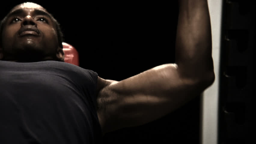 Muscular sweaty man lifts weights in the shadows. Close up