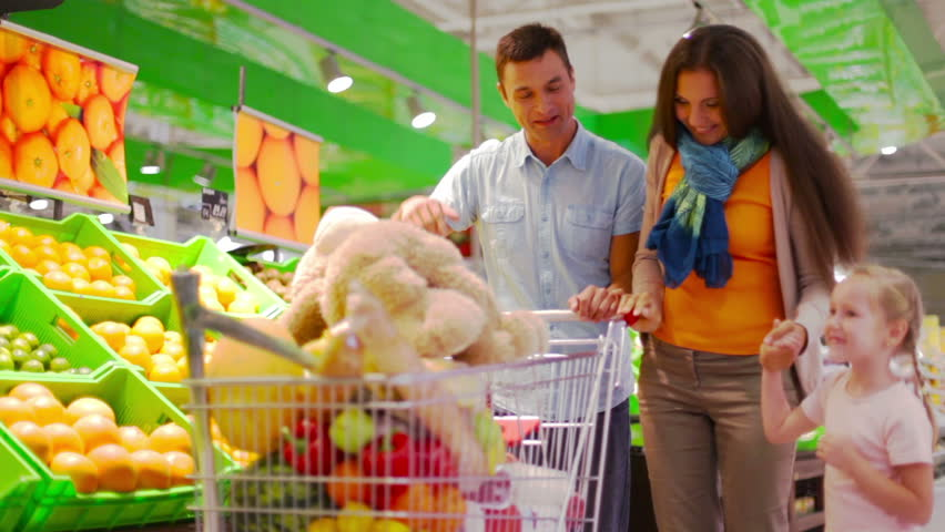Lovely girl bringing a teddy bear to her parents in the supermarket