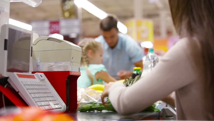 Father and daughter paying for groceries at the checkout counter - HD stock video clip