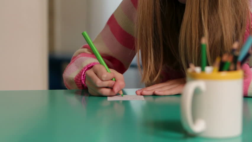 Close up of a serious young girl while drawing on paper - HD stock video clip