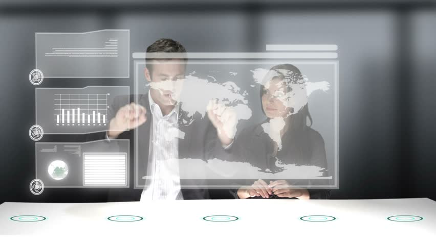 Two business professionals use a computer generated video wall to look over the stats of their company. Medium CG shot.