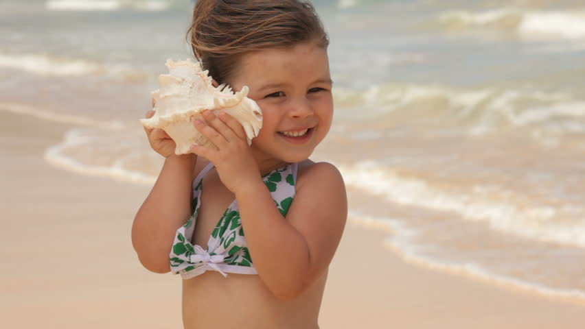 Young girl standing at beach holding shell up to ear