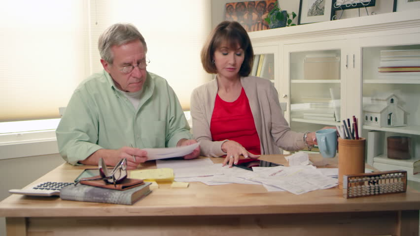 A married couple sit with a pile of bills and try to figure out how they are going to pay them all. Medium shot.