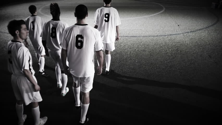 A soccer team walks out to the pitch in dramatic lighting
