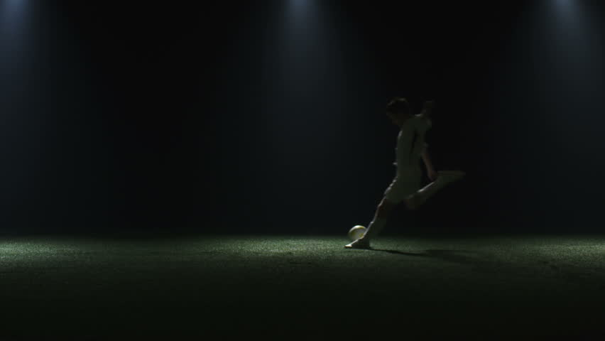 A soccer player runs and kicks the ball out of frame in the shadows