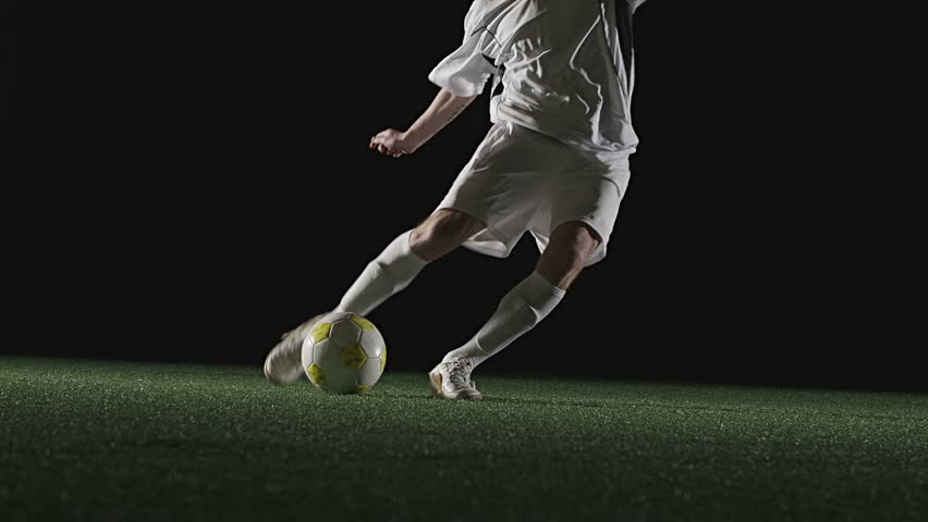Low angle view of a soccer player running up and kicking a ball very hard - HD stock video clip