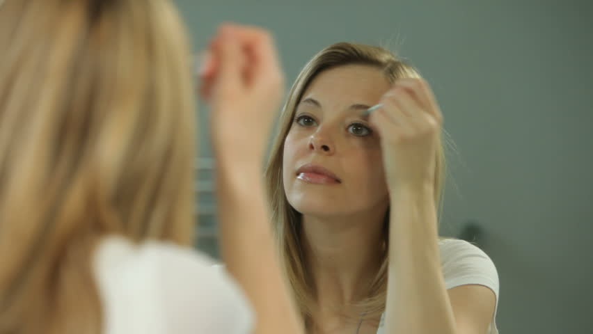 Woman doing makeup in mirror - HD stock footage clip