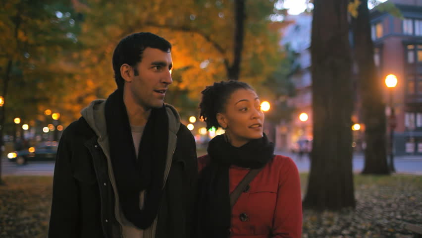 A cute couple walk through a park in a city talking. Medium shot. - HD stock footage clip