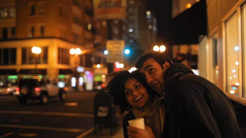 A cute young couple walk through a city at night together. Medium shot. - HD stock video clip