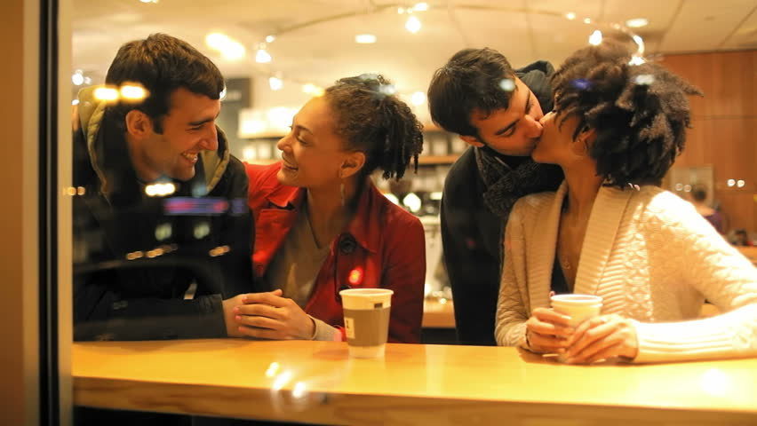 Two young guys walk into the cafe and greet the two women that are drinking coffee. Medium shot. - HD stock footage clip