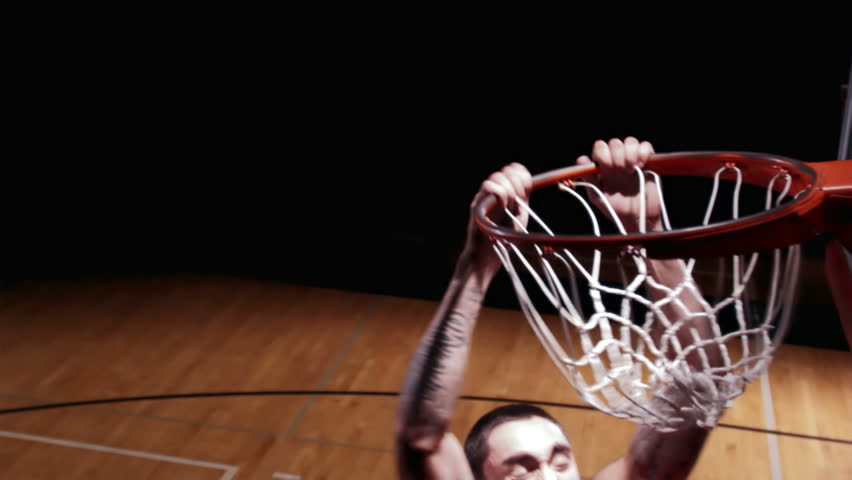 A close up of a basketball player running up and dunking the ball