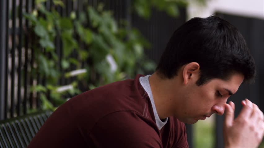 A young adult male sits on a bench expressing sadness. medium shot. - HD stock footage clip