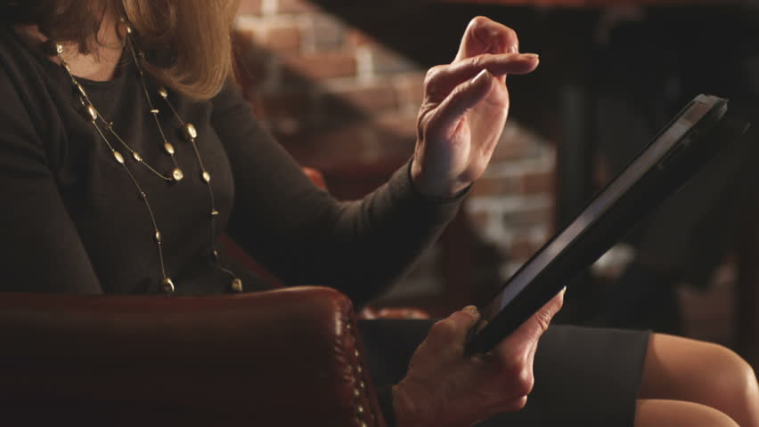 A woman uses the touch screen of a tablet computer. Close up shot. - HD stock footage clip