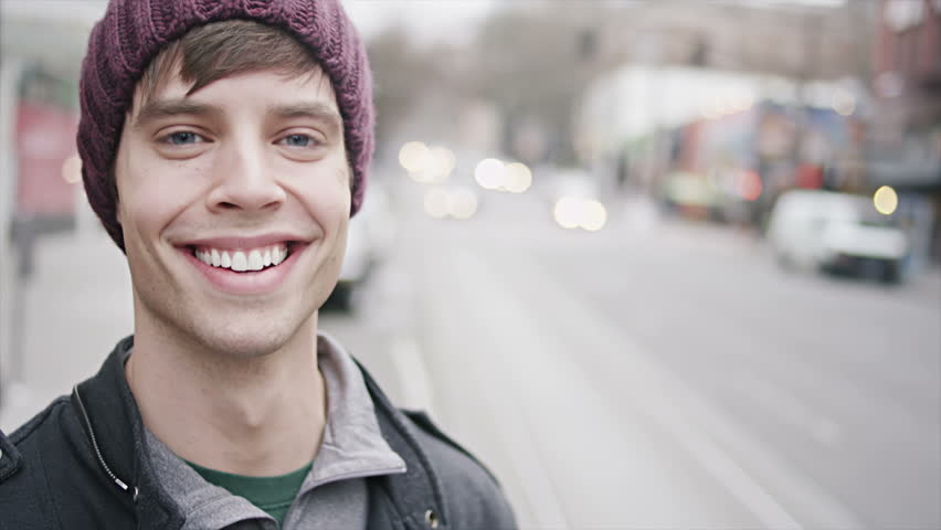 As a young man waits for his bus, he turns and smiles big for the camera. Close up shot.
