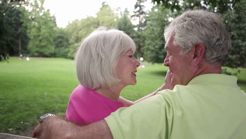 Senior couple sitting on bench facing away from the camera. Medium shot. - HD stock footage clip