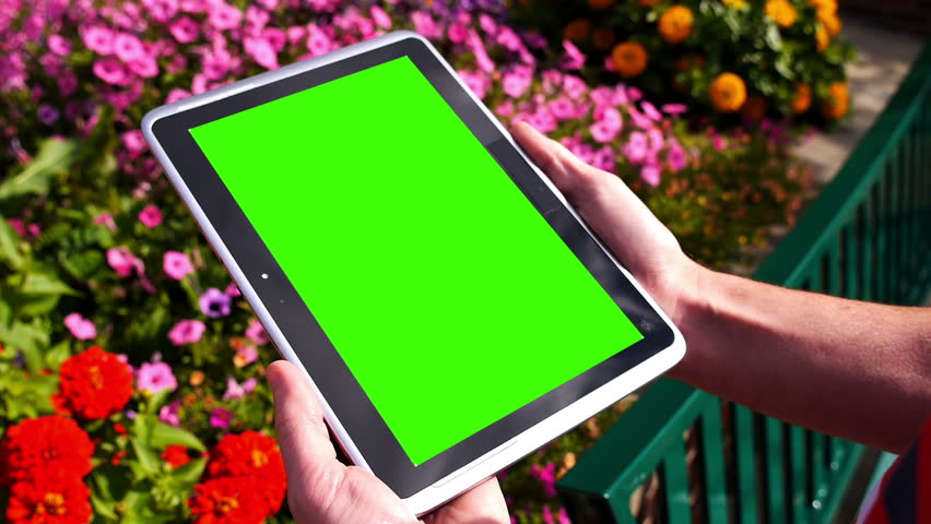 A man holds a blank tablet PC in portrait orientation with a green screen for your own custom content. Optional luma matte and corner markers included for advanced motion tracking. - HD stock footage clip