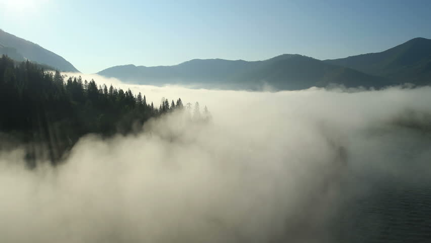 Aerial View. Flying over the high mountains in beautiful clouds . Aerial camera shot.Air clouds. Altai, Siberia.