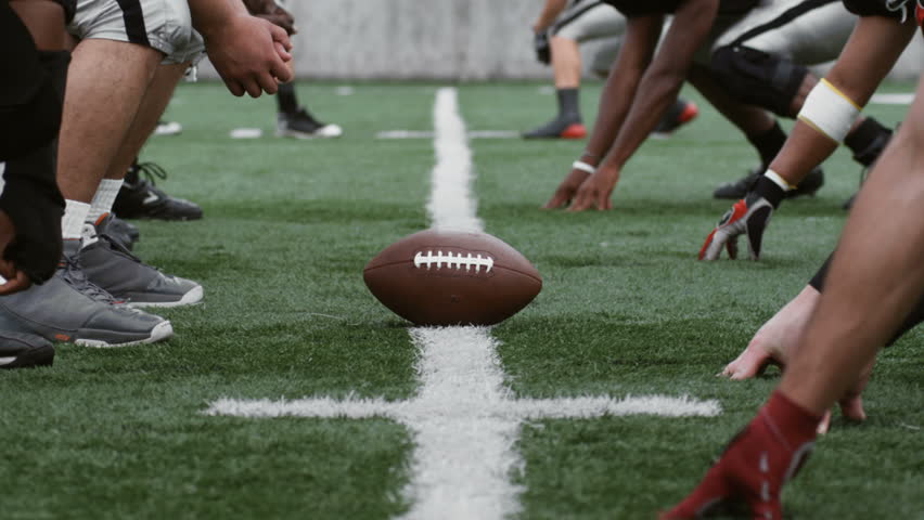 Opposing football teams line up for a play. - HD stock footage clip