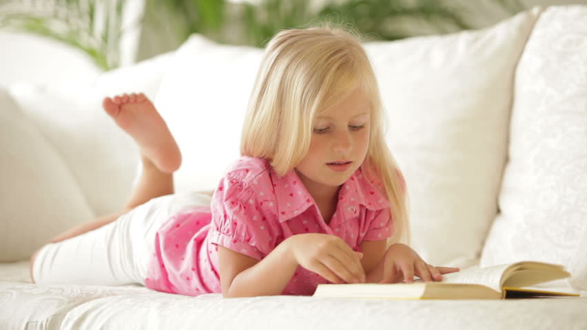 cute little girl lying on sofa reading book and smiling erin cute as a button loveseat world market