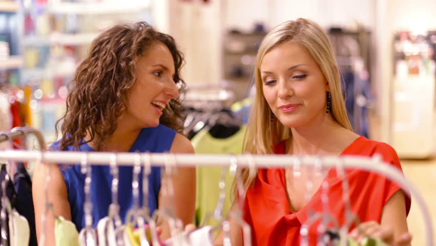 Young women choosing clothes hanging on the racks